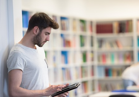 arab adult: student preparing exam and learning lessons in school library, making research on tablet  and browse internet