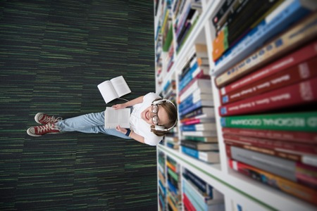 a study: female student study in school library, using tablet and searching for information's on internet. Listening music and lessons on white headphones