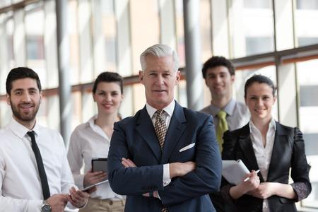 Portrait d'homme d'affaires senior en tant que chef de file à l'intérieur de bureau lumineux moderne, groupe de jeunes en arrière-plan en tant qu'équipe Banque d'images
