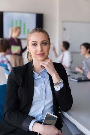 small office: portrait of young business woman at modern startup office interior, team in meeting group in background Stock Photo