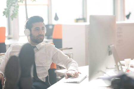 cubicle: happy young arabian  business man with beard  listening music on headphones at modern startup office