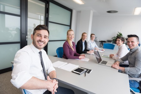 Startend bedrijf, jonge creatieve mensen groep brainstormen over team vergadering op moderne kantoor interieur. Met behulp van laptop, tablet en smartphone computer om op te merken ideeën plannen en projecten