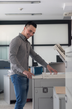 copier: young business man copy documents on copy machine at modern startup office interior, casual clothes