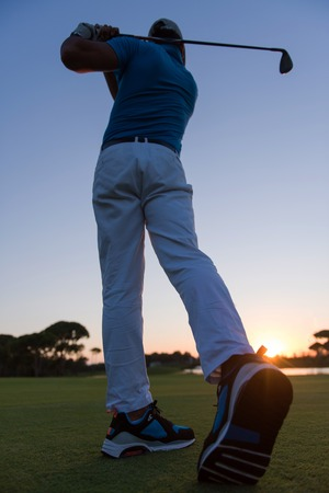 plan éloigné: golfer hitting long shot with driver on course at beautiful sunset Banque d'images