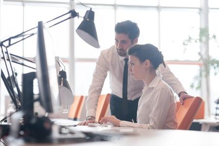 ビジネス カップルは、モダンなスタート アップ オフィスでのプロジェクトに一緒に働いて