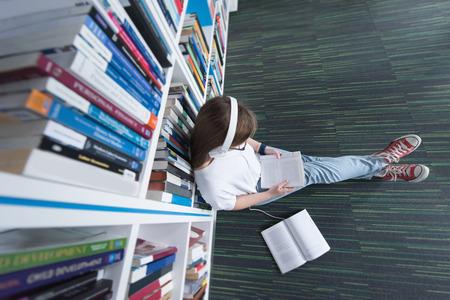 학교 도서관에서 여성 학생 학습, 태블릿을 사용하여 정보를 인터넷에서의 검색. 흰색 헤드폰에 음악과 수업을 듣기