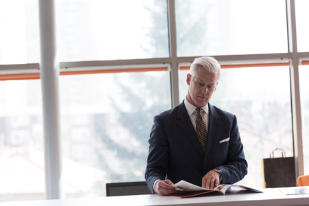 article of clothing: senior business man reading magazine at modern bright office