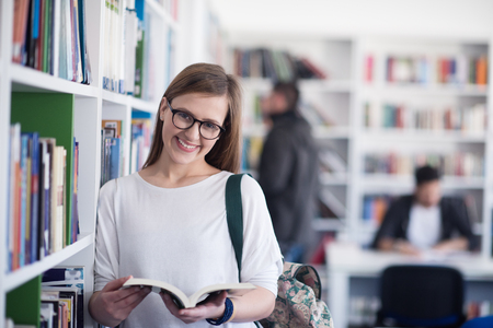 famale: portrait of smart looking famale student girl  in collage school library reading book Stock Photo