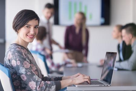 Mujer de negocios joven en el interior de la oficina moderna arranque trabaja en el ordenador portátil, el equipo desenfocada en el encuentro, el grupo de personas en el fondo