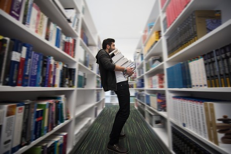 trabajando duro: Estudiante que sostiene muchos libros en la biblioteca de la escuela. El trabajador duro y el concepto de persistencia. Foto de archivo