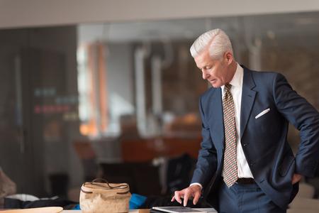 rapports homme d'affaires de lecture supérieurs sur ordinateur tablette à l'intérieur moderne de bureau