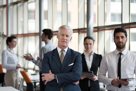 近代的な明るいオフィス インテリアでリーダーとして上級ビジネスマンの肖像、若者グループのチームとしてバック グラウンドで