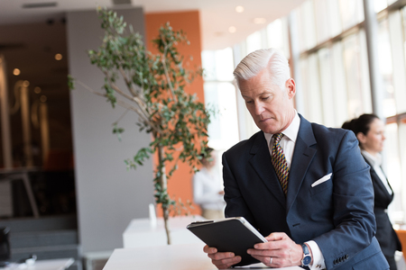 business man phone: handsome senior business man with grey hair working on tablet computer at modern bright office interior