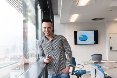 good looking: relaxed young businessman using smart phone at modern startup business office meeting room  with big window and city in backgronud