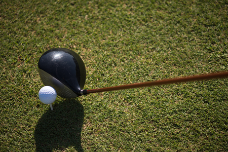 point of view: golf club and ball in grass on course preparing for shot