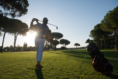 shot: handsome sporty man, golf player hitting shot with club on course at beautiful morning