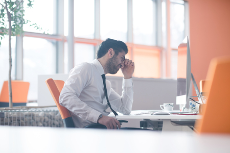 frustrated young business man working on desktop  computer at modern startup office interior Stock Photo