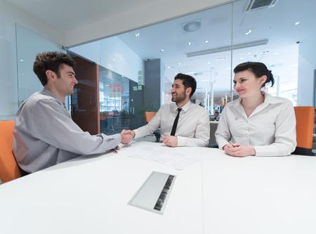 apreton de mano: firmar el contrato de socios de nuevo, joven pareja en reunión de trabajo con el agente de seguros de vida y préstamo bancario al interior de la oficina moderna