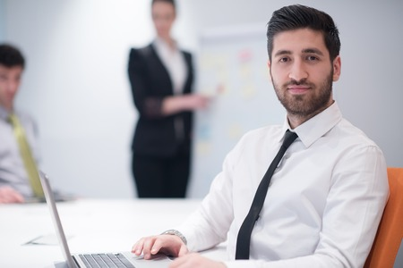 arab: portrait of young modern arab business man with beard at office meeting room,   group of  business people  on brainstorming and  making plans and projects on white flip board in  background