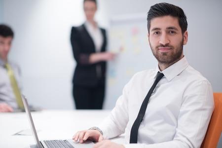 portrait de jeune homme d'affaires arabe moderne avec la barbe au bureau salle de réunion, un groupe de gens d'affaires sur remue-méninges et de faire des plans et des projets sur tableau blanc flip en arrière-plan