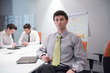 young man portrait: portrait of young business man with curly hair and  at modern bright office  interior with big windows in background
