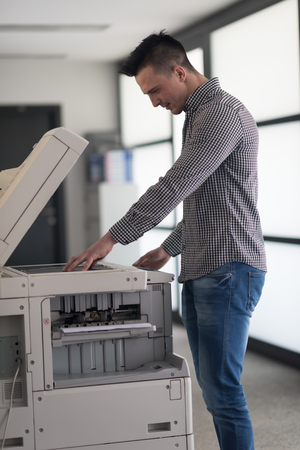 photocopier: young business man copy documents on copy machine at modern startup office interior, casual clothes
