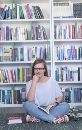 famale: smart looking famale student girl  in collage school library reading book Stock Photo