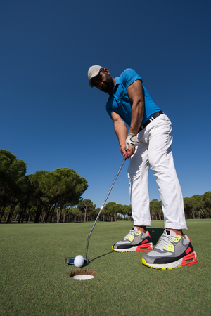 wide angle lens: golf player hitting shot with driver on course at beautiful sunny day with wide angle lens