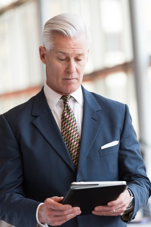white suit: handsome senior business man with grey hair working on tablet computer at modern bright office interior