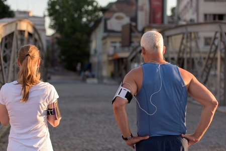 hombres maduros: los pares que activa lista de reproducción de verificación en la ruta teléfono y un plan antes de la mañana corriendo entrenamiento con la salida del sol en el resplandor de la ciudad y el sol en el fondo
