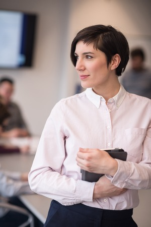 successful woman: young hispanic businesswoman portrait with  tablet computer at modern startup business office interior, people group on team meeting blured in background Stock Photo