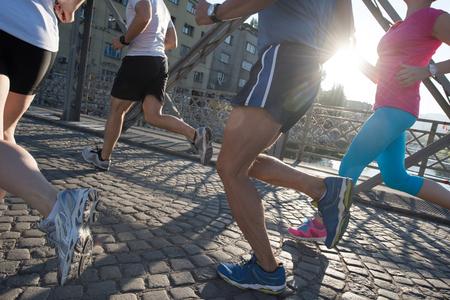 Leutegruppen-Joggingläuferteam auf Morgentrainingstraining mit Sonnenaufgang im Hintergrund