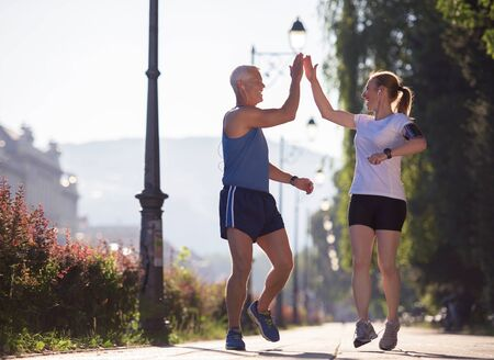 outdoor training: jogging friends couple congratulate and happy to finish their morning workout