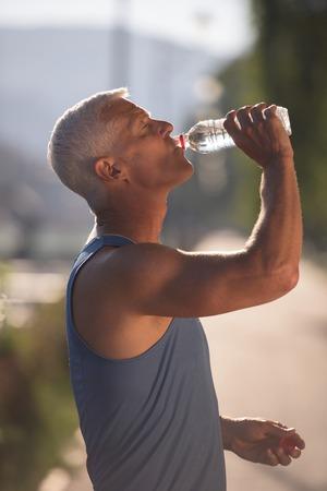 running man: handsome senior jogging man drinking fresh water from bottle after mornig run