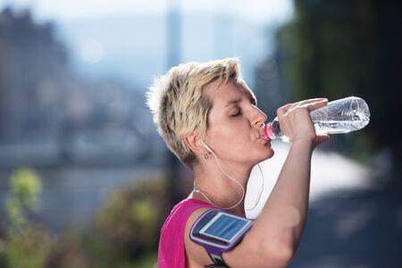 hacer footing: mujer joven que bebe un agua después de la salida del sol del mornig entrenamiento para correr en segundo plano de la ciudad