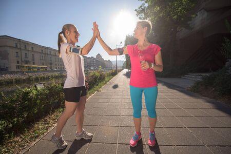 hacer footing: trotar amigos par felicitar y contento de terminar su entrenamiento de la mañana