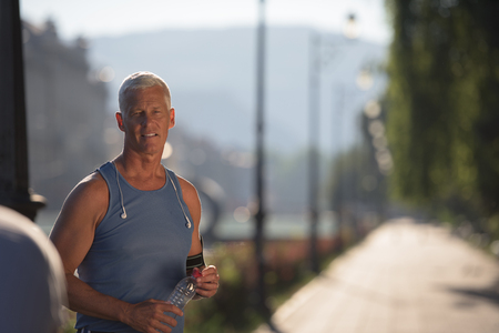 portrait of handsome senior jogging man while relaxing  and take break after morning run Stock Photo