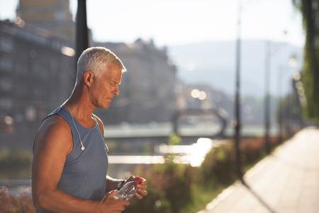 hacer footing: apuesto hombre correr mayor que bebe el agua dulce de la botella después del rodaje del mornig