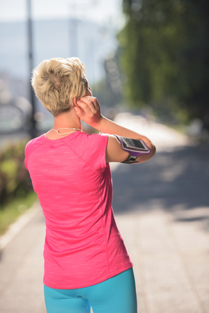 bluetooth: jogging woman setting music and running route on  smart phone putting  earphones before morning run