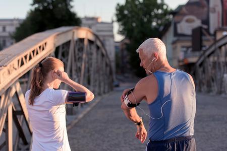 joggen paar check muziek afspeellijst op telefoon en plan route voor de ochtend met training met zonsopgang in de stad en zon flare op achtergrond Stockfoto