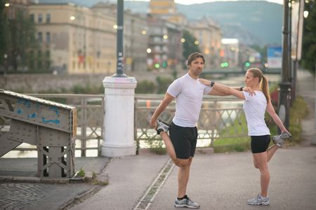 PRETTY WOMEN: jogging couple warming up and stretching before morning running in the city