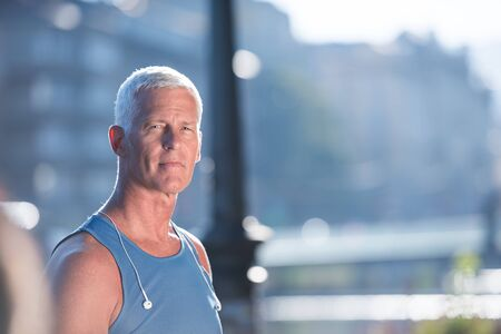 elderly exercise: portrait of handsome senior jogging man while relaxing  and take break after morning run Stock Photo
