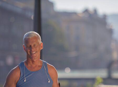 Porträt der schönen Senior Joggen Mann beim Entspannen und nehmen Pause nach dem morgendlichen Lauf