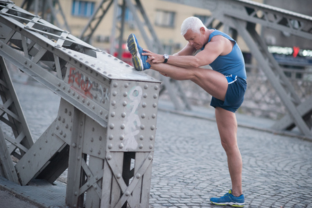 man legs: handsome senior man stretching and warming up before jogging exercise at early mornig