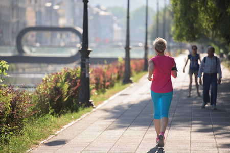 mature woman: sporty woman running on sidewalk at early morning with city  sunrise scene in background Stock Photo