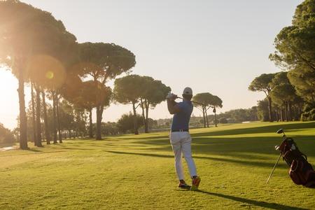 ハンサムなスポーティな人、美しい朝のコースのクラブでショットを打つゴルフ選手