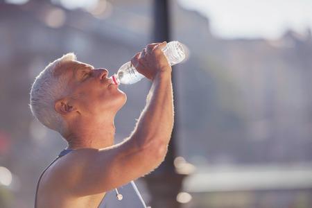 hombres maduros: apuesto hombre correr mayor que bebe el agua dulce de la botella después del rodaje del mornig
