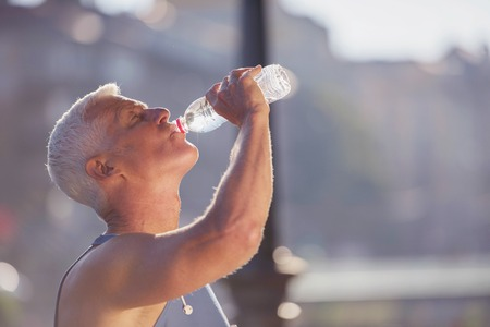 gutaussehend Senior frisches Wasser trinken Jogging Mann aus der Flasche nach mornig Lauf
