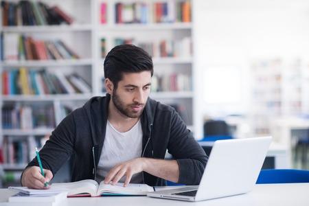 Student przygotowuje egzamin i lekcje w bibliotece szkolnej nauki, przez co badania na laptopie i przeglądać internet