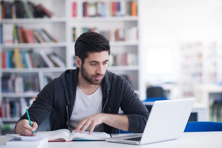Student Vorbereitung auf die Prüfung und Unterricht in der Schulbibliothek, so dass Forschung auf dem Laptop und surfen Internet-Lernen Lizenzfreie Bilder